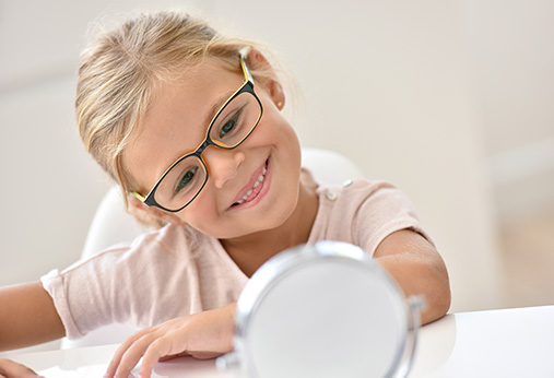 little girl trying on glasses